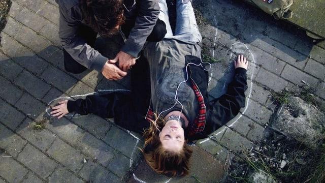 Mordopfer liegt am Boden mit Kreidelinie umzeichnet.