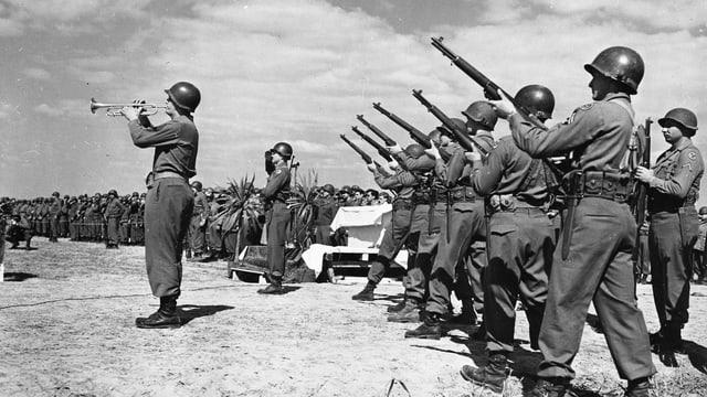 Soldaten mit Gewehren im 2. Weltkrieg. Davor ein Soldat der Trompete spielt.