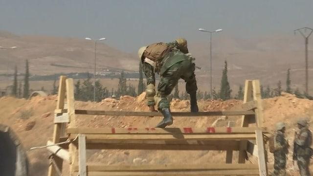 Soldat springt über ein Hindernis. Im Hintergrund wüstenähnliche Landschaft.