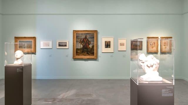 Blick in einen Ausstrellungsraum, an dem mehrere kleinere Bilder hängen und zwei Büsten in Glaskuben stehen.