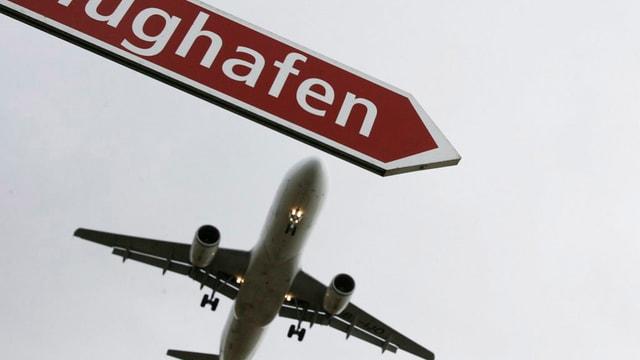 Ein Flugzeug und ein Wegweiser mit der Aufschrift Flughafen.