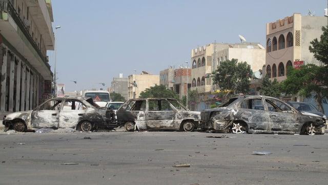 Drei ausgebrannte Autowracks nach Unruhen auf einer Strasse in Tripolis