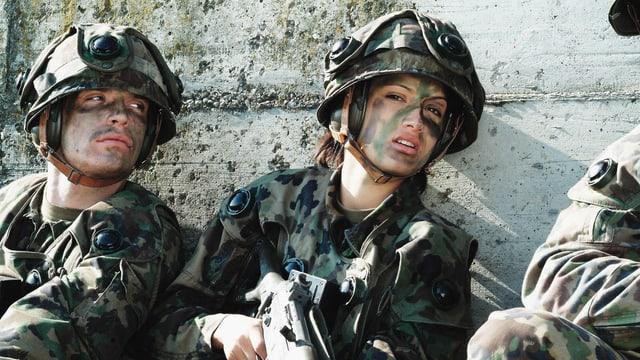 Ein Mann und eine Frau in Schweizer Militäruniform kauern hinter eine Mauer.