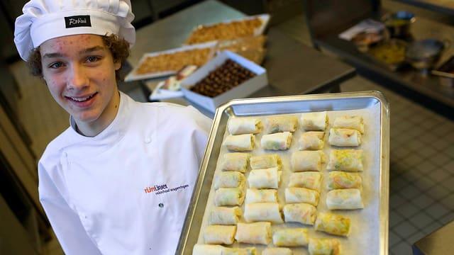 Ein junger Koch hält ein grosses silbernes Tablett in der Hand, auf dem sich zahlreiche Frühlingsrollen befinden.