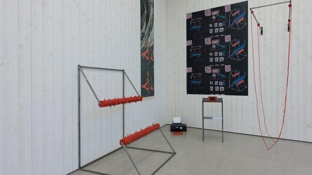 Eine Wand mit zwei dunklen Bildern und zwei metall Gebilden am Boden.