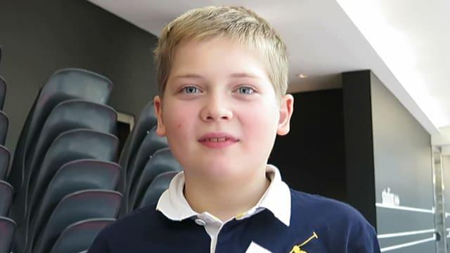 Ein blonder Junge in einem dunkelblauen Pulli