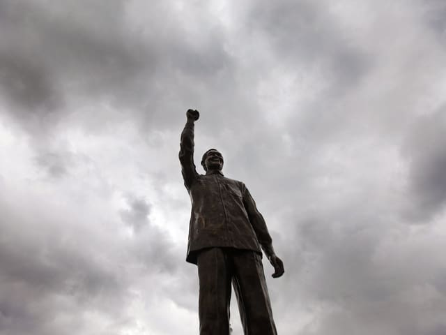 Statue von Nelson Mandela ragt in den dunkelgrauen Himmel