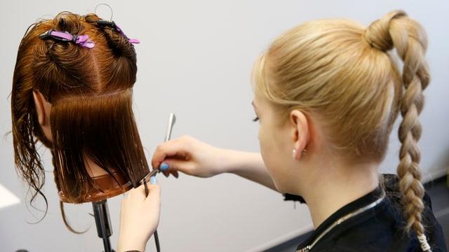 Eine junge Frau übt an einer Puppe eine Frisur zu machen.