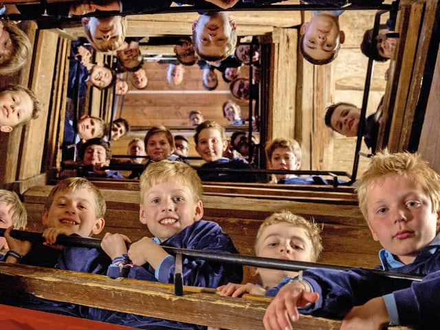 Singknaben positionieren sich auf einer Wendeltreppe der Reihe nach, so dass alle über das Treppengeländer hinunter zum Fotografen schauen können.