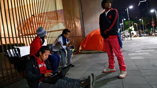 Drei Migranten aus Zentralamerika sitzen am Boden vor einem vergitterten Fenster, einer steht