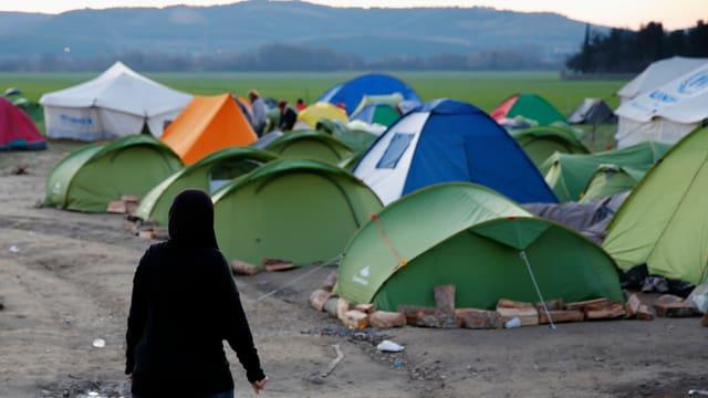 Frau vor Zelten eines provisorischen Flüchtlingscamps an der griechischen Grenze zu Mazedonien