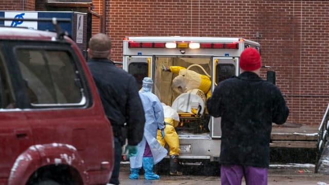 Helfer in Schutzkleidung transportieren Patienten