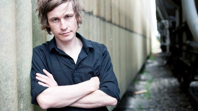 Autor Arno Camenisch lehnt sich im schwarzen Hemd an eine Wand.