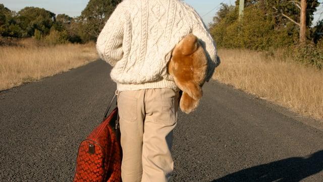 Kind allein auf der Landstrasse mit Gepäck