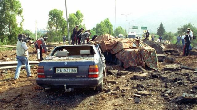 Zerstörte Autos, Polizisten stehen darum herum.