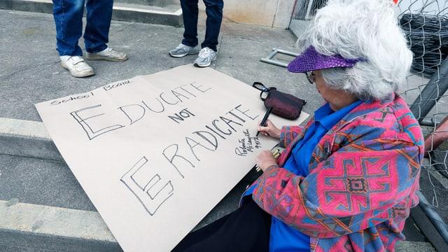Eine ältere Dame malt ein Transparent. Darauf steht: Educate not eradicate.