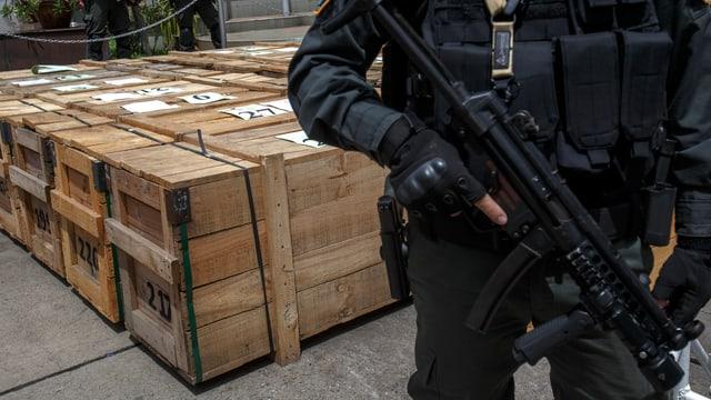 Ein bewaffneter Mann in schwarzer Uniform steht vor einer Reihe von Holzkisten.