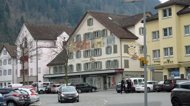 Ein Platz mit parkierten Autos, daneben eine Strasse und ältere Häuser.