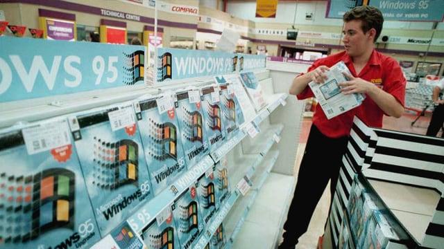 Ein Verkäufer stapelt Windows-95-Pakete auf.