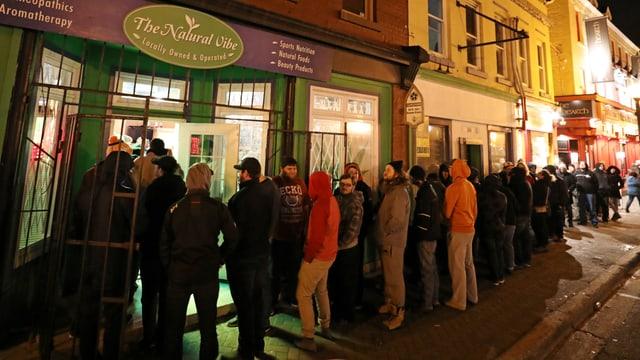 Menschen stehen Schlange vor einem Cannabis-Laden.