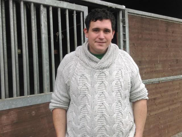 Robin Geisser, Geflügelzüchter aus Mörschwil, vor einem Stall mit Gänsen drin.