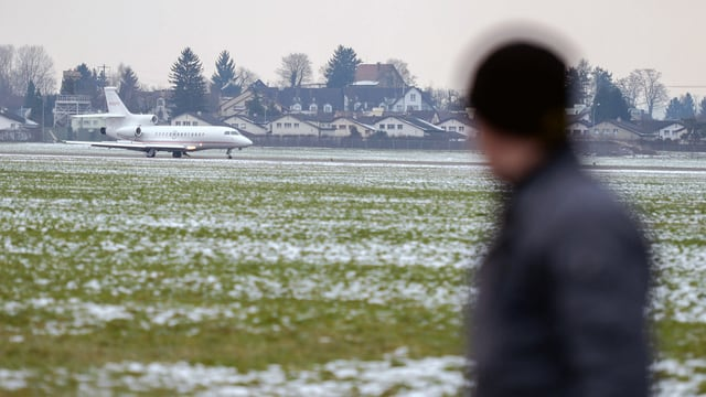 Ein Business-Jet landet mit WEF-Teilnehmern in Dübendorf, beobachtet von einem Beamten der Kantonspolizei Zürich.