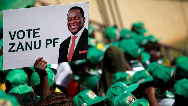 Menschenmenge mit grünen Hüten, ein Plakat mit Mnangagwa in der Menge.