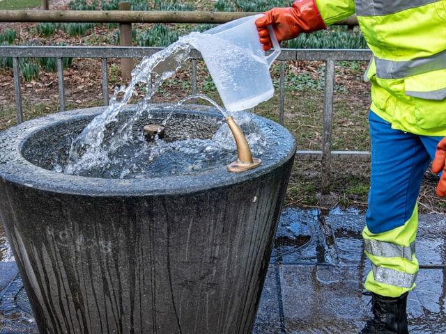 Mann reinigt einen kleinen Brunnen