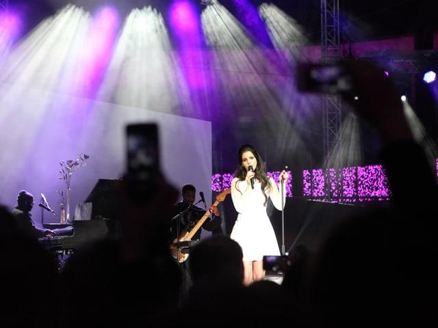 Die Sängerin Lana Del Rey in weissem Kleid und ihre Musiker auf der lila beleuchteten Bühne.