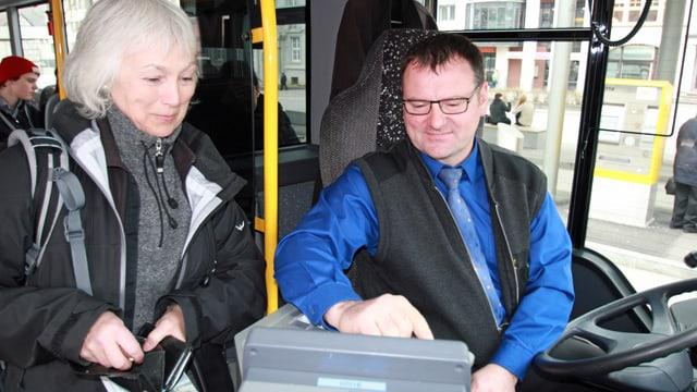 Ein Chauffeur in einem Schaffhauser Bus verkauft einer Kundin ein Billett