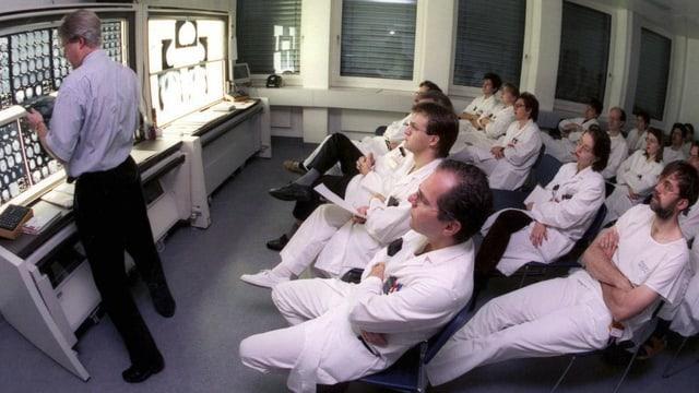 Ärzte in weissen Kitteln auf Stühlen schauen einem Ausbildner zu.