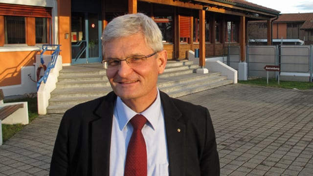 Andreas Naegeli steht vor einem Gebäude.