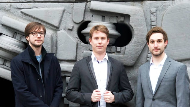 Drei Männer vor einem grauen Hintergrund