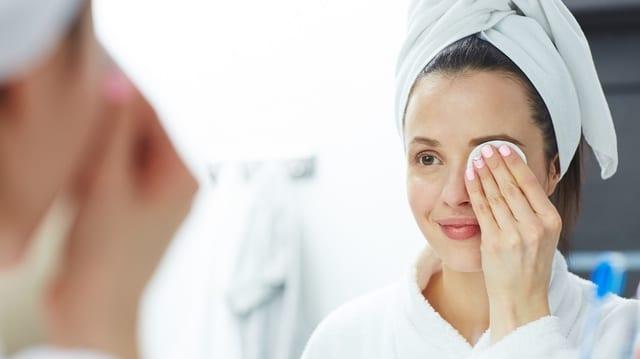 Frau schminkt vor dem Spiegel ihre Augen ab.