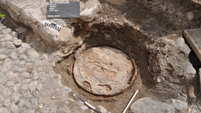 Eine Platte liegt freigeschaufelt inmitten von Steinen.