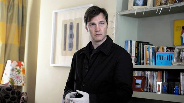 Ein Mann mit Gummihandschuhen steht in einem Zimmer.