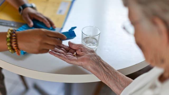 Eine Pflegerin gibt einer alten Frau Medikamente.