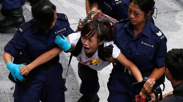 Zwei weibliche Sicherheitskräfte tragen eine junge Frau fort
