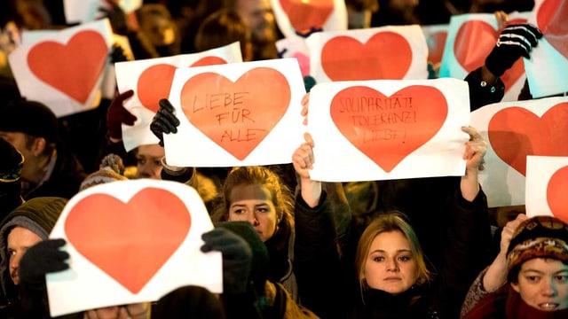 Menschen halten in Berlin Papierherzen hoch: «Gegen Dummheit und Angst vor Fremden».