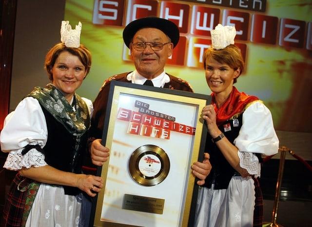 Mann hält goldene Schallplatte in die Kamera. Zwei Frauen in Trachten stehen ihm zur Seite.