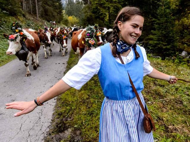 Eine Frau in Tracht kehrt mit den Kühen ins Tal zurück.