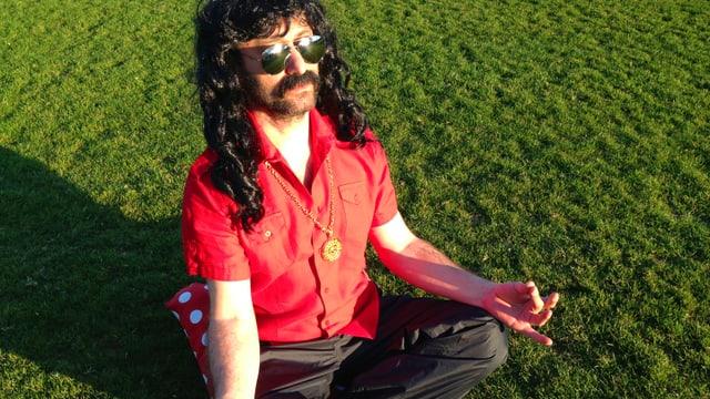 Ein Mann mit langen schwarzem Haar, weit geöffnetem Hemd und Sonnebrille sitzt im Lotussitz auf einer Wiese