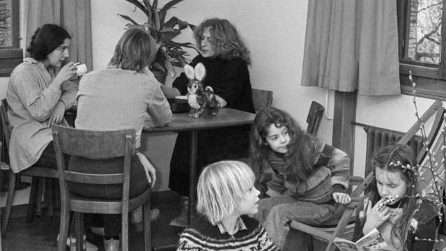 Drei Frauen sitzen an einem runden Tisch. Vor ihnen sind drei Kinder zu sehen.