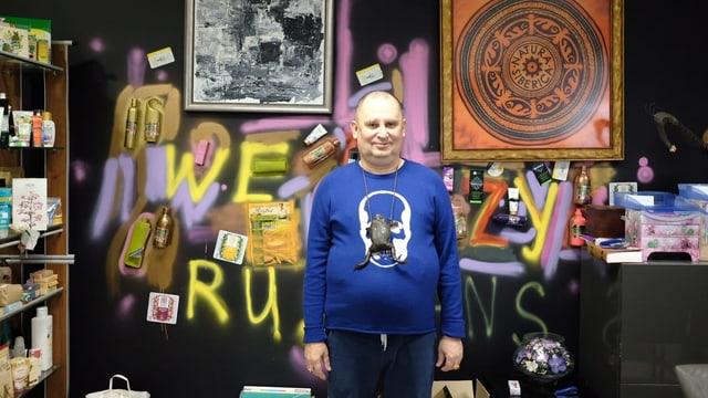 """Trubnikow in seinem Büro. Die Wand hinter ihm ist besprayt, es hängen Bilder. Man kann den gelben Schriftzug """"We crazy Russians"""" erkennen."""