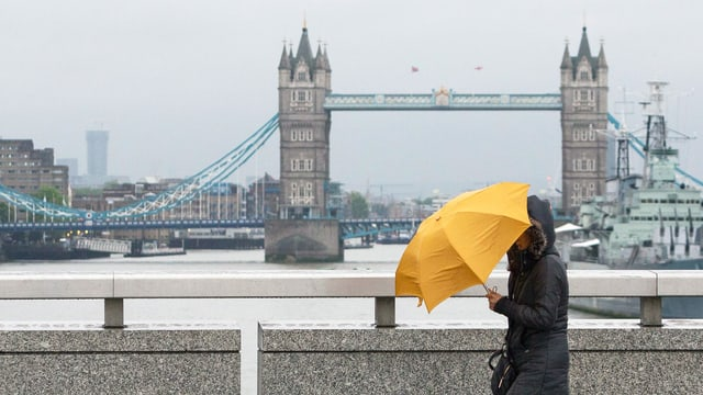 Frau mit Regenschirm läuft an der Tower Bridge vorbei.