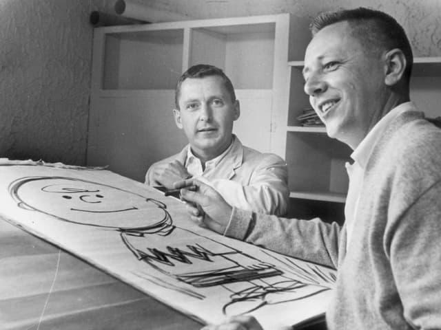 Schwarz-Weiss-Aufnahme: Ein Mann vor einem Tisch, auf dem eine Comiczeichnung eines Jungen zu sehen ist. Im Hintergrund ein Mann.
