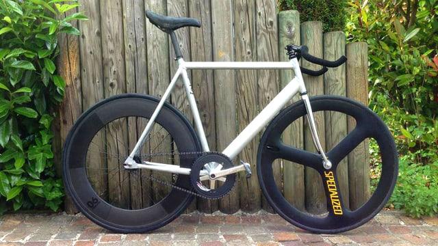 Single Speed Bike vor einer Holzwand.