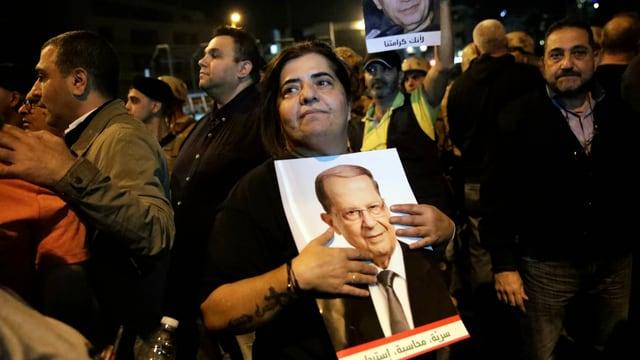 Frau hält Bild umarmt. Darauf ist Aoun zu sehen.