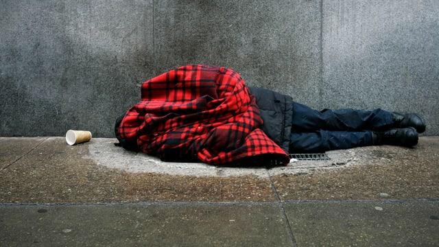 Ein Obdachloser liegt umhüllt in eine Jacke auf dem Boden.