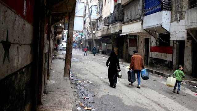 Menschen mit Kanistern in der Strasse von Aleppo.